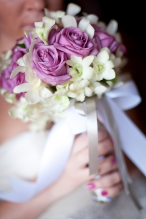 Wedding bouquet in brides hand photo