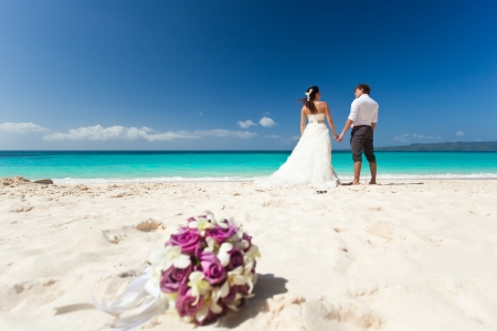 Wedding bouquet on wedding couple background, kissing at the beach  Stock fotó