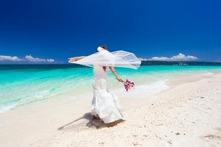 Happy dancing bride on beach in wedding dress
