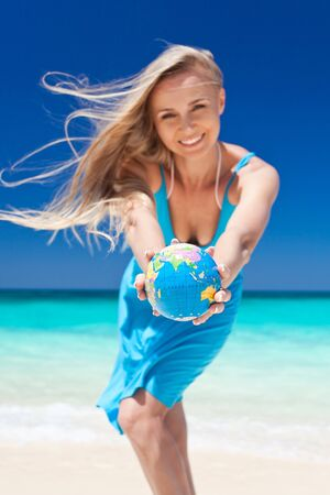 Happy woman holding a globe in hands on beach, smiling photo