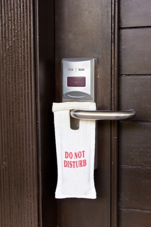 Hotel door with sign do not disturb photo