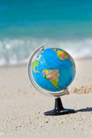 Globe on caribbean beach, travel concept  photo