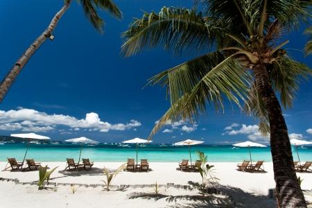 Sun umbrellas and chairs on tropical beach, Philippines, Boracay 스톡 콘텐츠