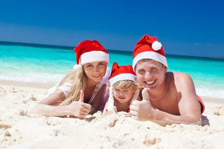 Happy family on beach in Santa hats, mother, father and little daughter. photo