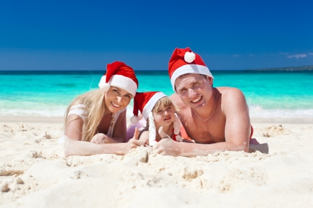 Happy family on beach in Santa hats, mother, father and little daughter  photo