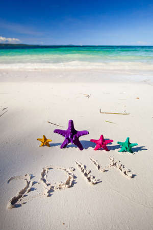 Numbers 2014 on white sandy beach with color starfishes photo