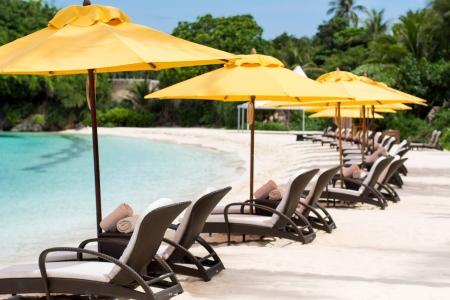 Sun umbrellas and beach chairs on tropical beach, Philippines, Boracay