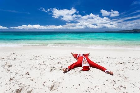 Santa Claus on beach relaxing, enjoying summer  photo