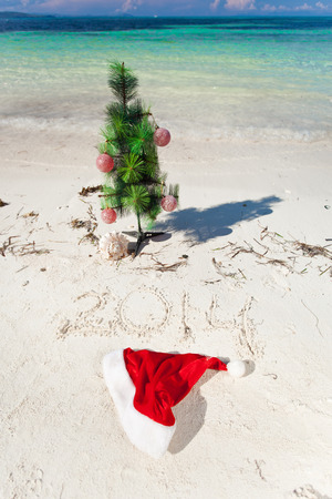 Summer New Year on beach with christmas tree and numbers 2014 photo