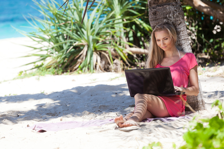 Blond girl with a laptop on tropical beach, freelance concept. Stock Photo - 22769214