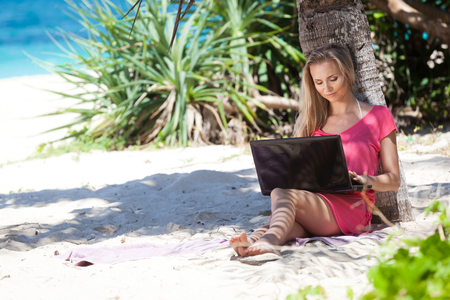 Blond girl with a laptop on tropical beach, freelance concept. Stock Photo - 22769215