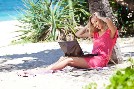 Blond girl with a laptop on tropical beach, freelance concept. Stock Photo - 22769216