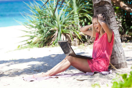 Blond girl with a laptop, working on tropical beach, freelance concept. Stock Photo - 22769218