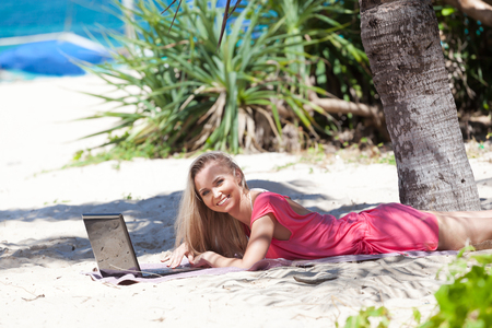 Blond girl with a laptop on tropical beach, freelance concept Stock Photo - 23218380