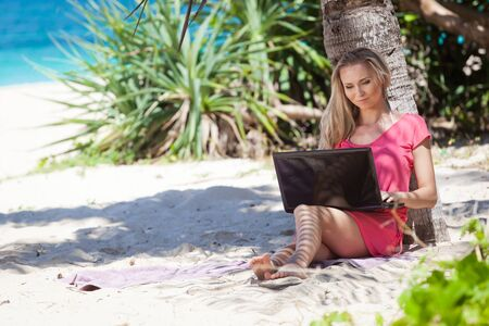 Blond girl with a laptop on tropical beach, freelance concept  photo