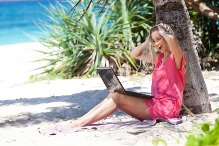 Blond girl with a laptop on tropical beach, freelance concept Stock Photo - 23218383