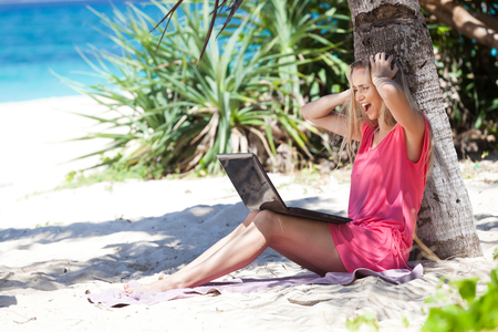 Blond girl with a laptop, working on tropical beach, freelance concept Stock Photo - 23218384
