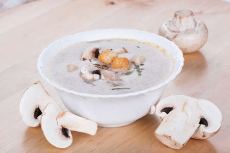 Mushrooms cream soup with agaric, closeup on wooden table photo