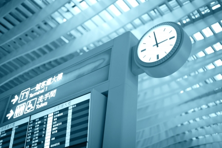 delay:  Big airport clock close to arrival board in airport terminal. Travel concept.