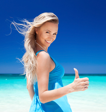 okey: Happy blond girl on beach, showing okey sign  Vacation concept