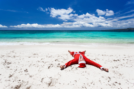 Santa Claus on beach relaxing, enjoying summer