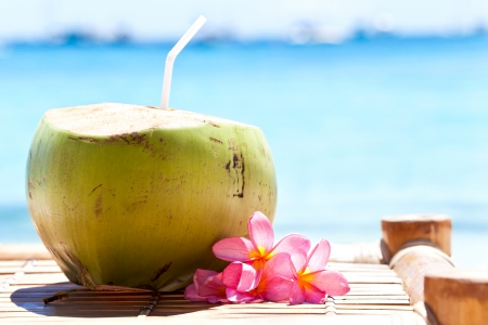 dominican: Tropical fresh coconut cocktail decorated plumeria on white beach Stock Photo