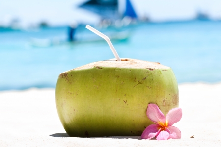 Tropical fresh coconut cocktail decorated plumeria on white beach photo