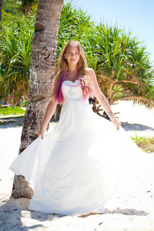 Beautiful bride in wedding dress on tropical beach photo