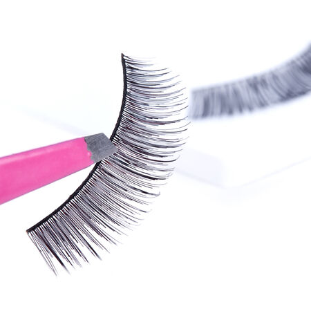 pincers: False lashes and pink pincers, closeup on white background