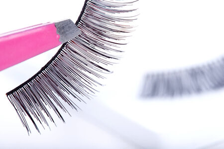 False lashes and pink pincers, closeup on white background  photo