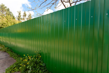 fence panel: New green metallic fence in village