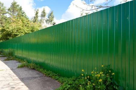 industrialized: New green metallic fence in village