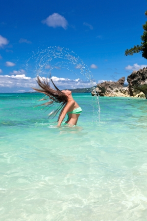 Woman in tropical sea waving hair and splashing out a water photo