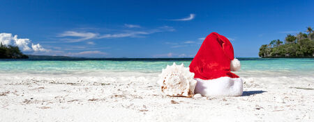 Red Santa Claus hat on beach with seashell, Travel Christmas concept photo