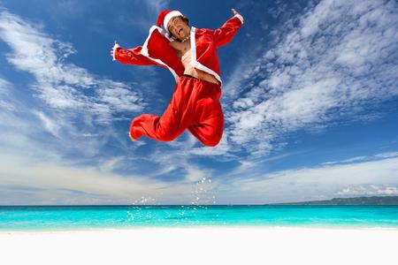 bahamas celebration: Santa Claus jumping on beach