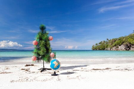 Christmas tree and Santa hat on perfect beach photo
