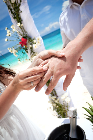 Bride putting a wedding ring on groom's finger, tropical wedding photo