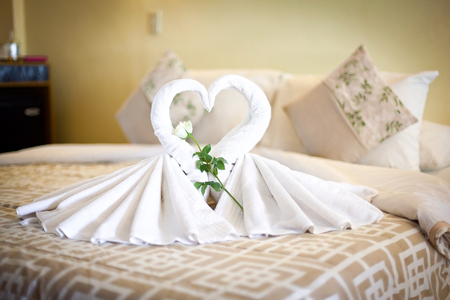 heart suite: Two white towels swans on bed sheet, decorated rose and heart in hotel room Stock Photo
