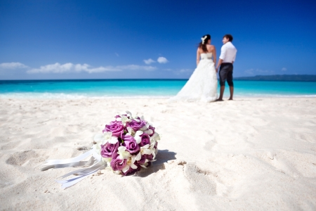 Wedding bouquet on wedding couple kissing at the beach photo