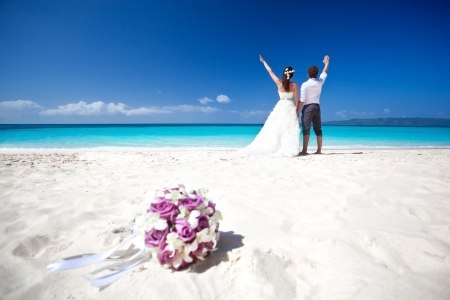 Wedding bouquet on wedding couple background, kissing at the beach