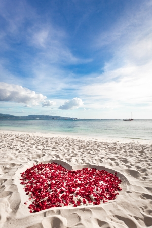 beaches: Heart of roses petals on tropical sandy beach. Nobody. Love concept