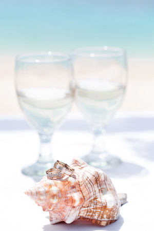 Wedding rings on seashell and glass of champagne, on tropical beach photo
