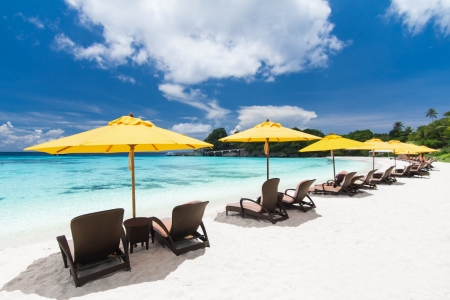 Sun umbrellas and chairs on tropical beach