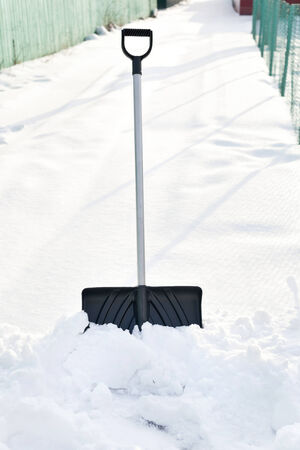 Shovel in snow, ready to removal snow, outdoors photo