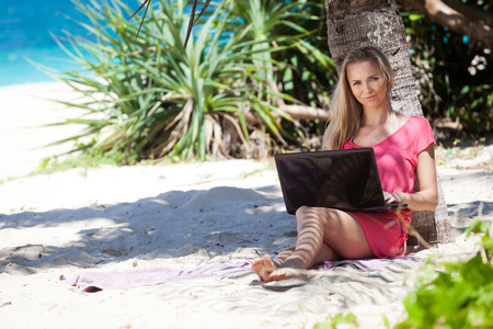 Blond girl with a laptop on tropical beach, freelance concept. photo