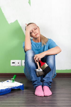 Tired woman with paint tools in hand Stock Photo