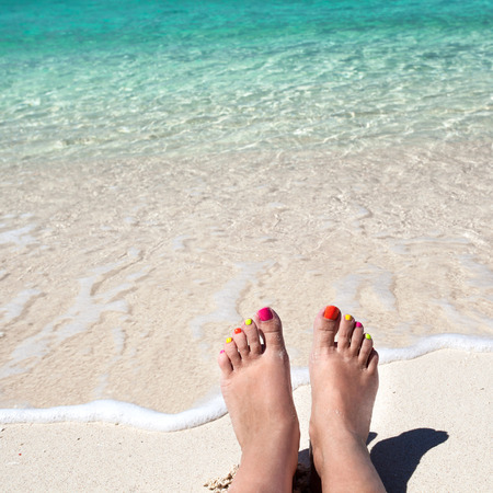 Woman legs lying on tropical sandy beach  photo