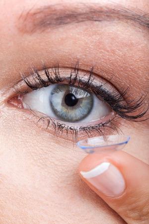 Woman eye with contact lens applying, macro Standard-Bild