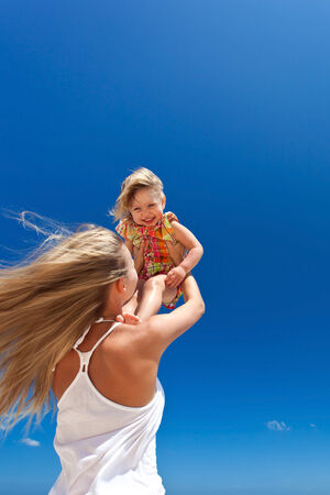 Mother throwing her daughter in air at the tropical beach photo
