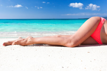 Tan slim legs lying on white sandy beach near sea photo